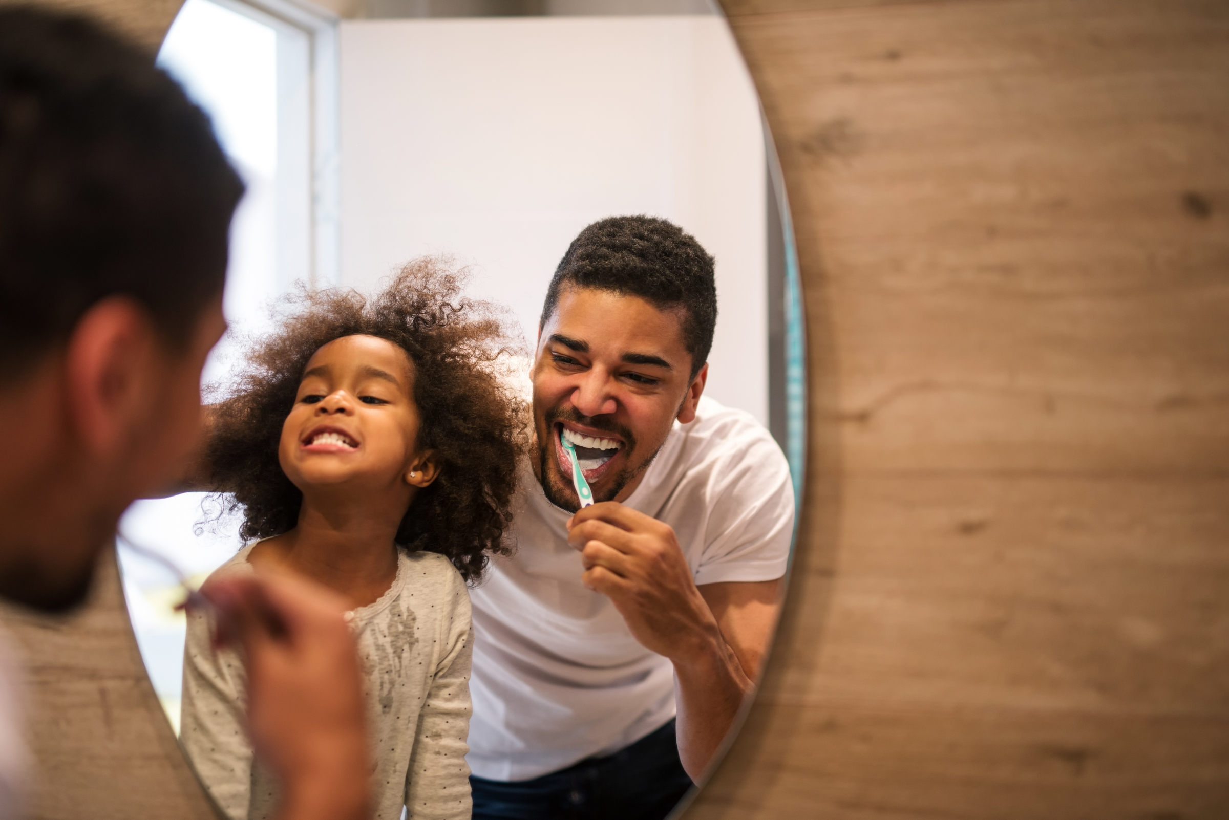 Father and daughter brushing teeth in front of bathroom mirror