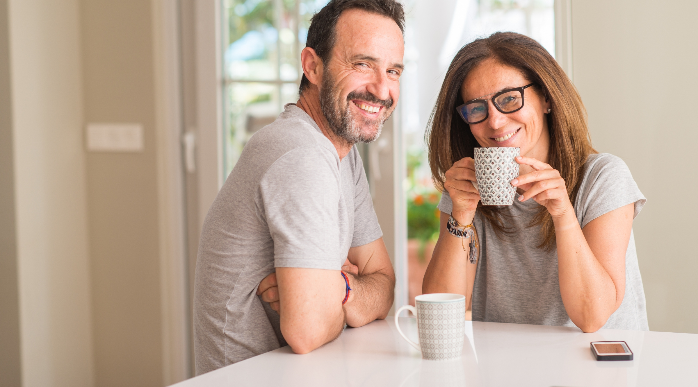 Middle Aged Couple Smiling and Drinking Coffee