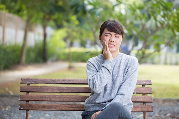 Woman with jaw pain, sitting on a park bench